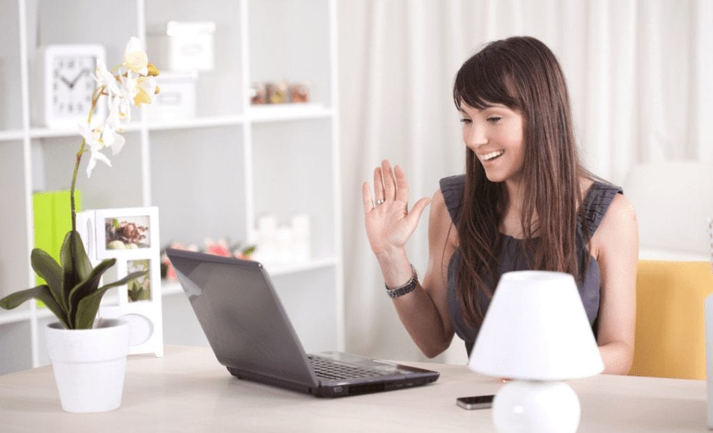 set boundaries with clients: woman waving hand at computer